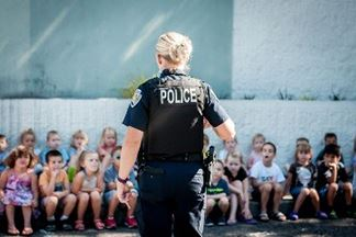 BPD officer with her back to the camera presents to a large group of young children.