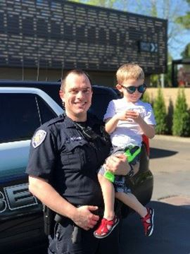 BPD officer holding young boy who is dressed for summer and wearing sunglasses.