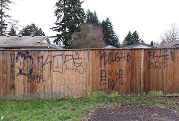 Gang tagging on residential wooden fence.