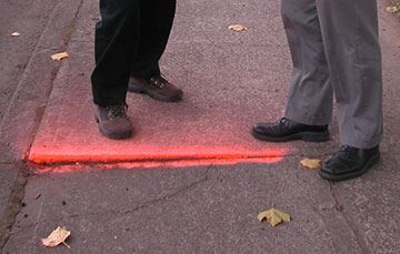 Two pairs of feet stand near an uneven sidewalk highlighted with neon red paint.