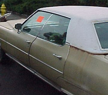An older in poor condition automobile with a red warning sticker on the driver's side window.