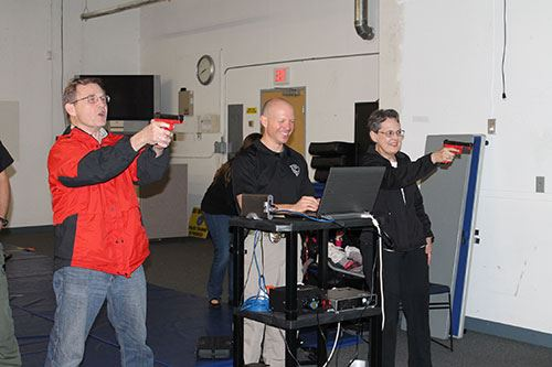 Photo of Beaverton police officer assisting Citizens Academy students with firearms training.